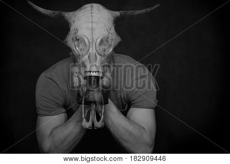 A mystical, fantastic photo - a double exposition - a man in a gas mask and a bull's skull