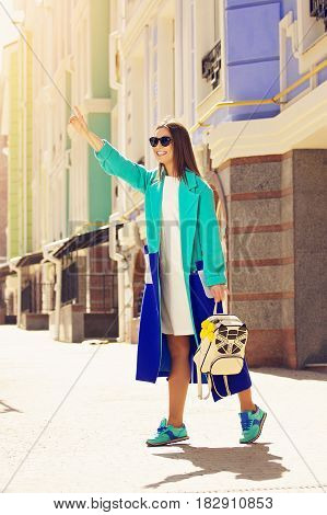Taxi, I Am Here. Fashionable, Young And Beautiful Girl In Blue Coat And Sunglasses Calling Taxi On T