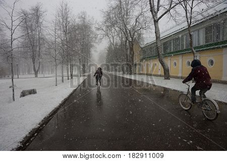 Two Persons On Bicycles Running Out Of A Weather Phenomena - Snowfall In Late April Near Moscow