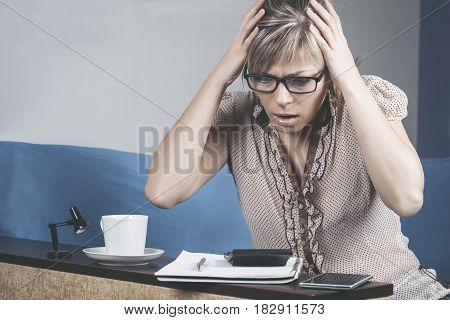 shocked crazy woman checking expensive electricity and household bills sitting on sofa in the living room at home. finance interior and domestic housework concept.