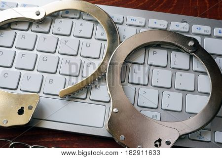 Hacking concept. Hand cuffs on the keyboard.