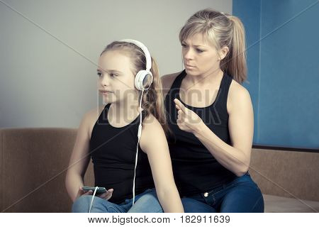 Beautiful woman is scolding her teenage daughter girl is listening to music in headphones and ignoring her mom.