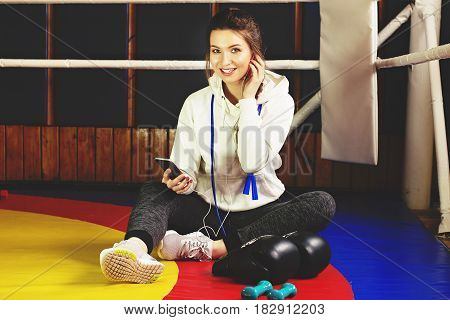 Smiling Beautiful Boxing Girl Using Her Phone In The Ring. Training At The Gym. Sporty Female Doing