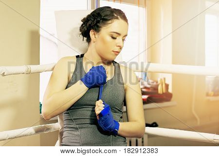 Portrait Of Beautiful Boxing Girl Wrapping Boxing Wraps In The Ring. Training At The Gym. Sporty Fem