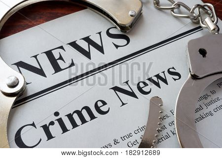 Newspaper with title crime news and handcuffs.