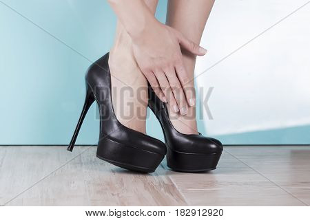 Tired and aching female feet after walking in high-heeled shoes.
