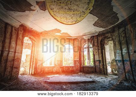 Ancient ruined abandoned manor or mansion, inside interior, round hall in sunlight