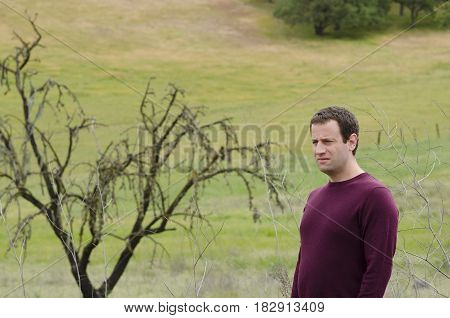 Man in deep thought in an open grassy field with a bare tree in the background.