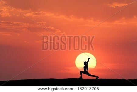 Silhouette of a standing sporty woman practicing yoga with raised up arms on the hill on the background of yellow sun and orange sky with clouds. Landscape with girl at sunset. Fitness and lifestyle