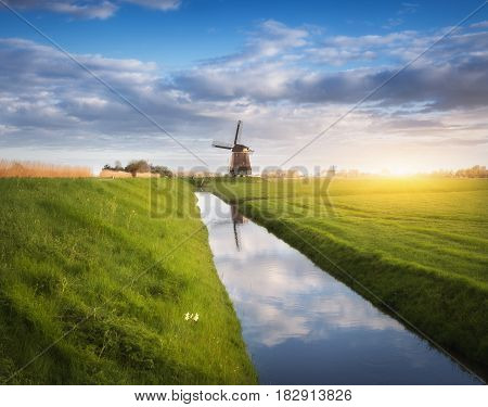 Rustic Landscape With Dutch Windmills Near The Water Canals