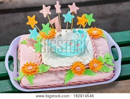 Birthday cake with colorful flowers stars and diadem