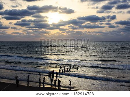 Silhouettes of a group of islamic people against the evening sea and sky. Tel Aviv Israel