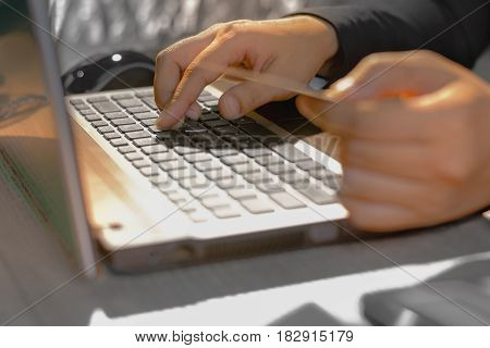 Young woman holding credit card on laptop for online shopping concept.