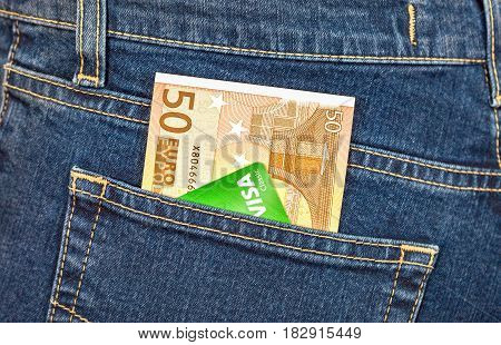 Moscow Russia - November 27 2016: Banknote 50 euro and credit card Visa sticking out of the back jeans pocket