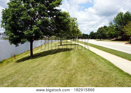 A view of a lawn between a small man-made lake and Wesmere Parkway in Joliet, Illinois during August.