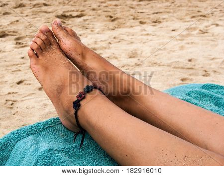 A pair of beautiful feet of a young lady stretched out on beach chair