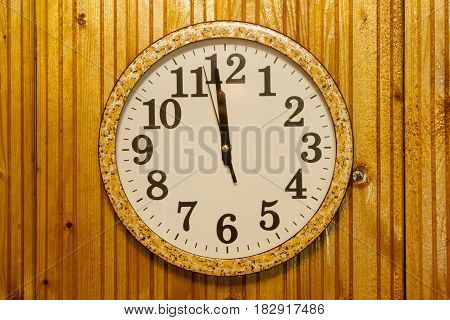 shot of clock on wooden wall shows midnight