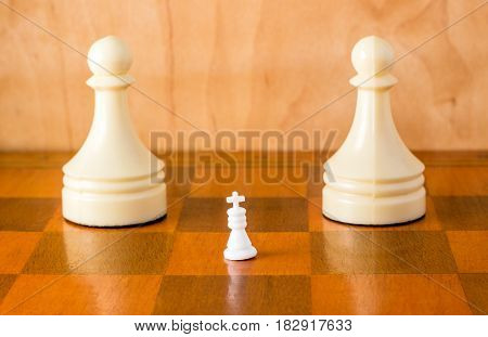 White chess king and pawns on a wooden board an ancient popular board game