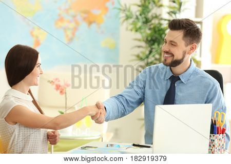 Adventure concept. Young woman visiting travel agency