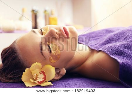 Young woman relaxing with collagen facial mask in spa center
