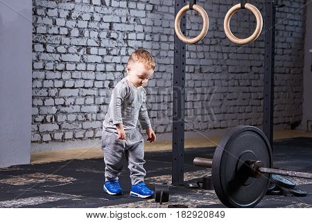 Little cute boy in the grey sportwera standing near barbell against brick wall in the cross fit gym. Sporty child in the blue sportive shoes. Rearing in the healthy lifestyle. Concept of the active child's life.