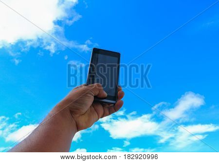 male hand holding mobile phone closeup or smartphone on blue sky background