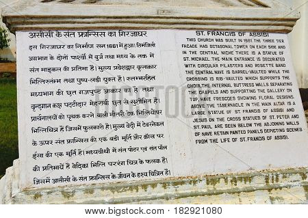 Old Goa, India - November 13, 2012: Tourist stone sign for tourists in two languages near famous landmark - Roman Catholic Church of St. Francis Assisi, Old Goa, India.