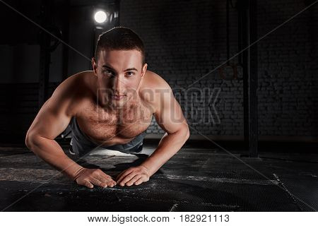 Young muscular man in the sportwear doing a pushups against brick wall at the crossfit gym. Close-up horizontal photo. Body, muscle and abs. Healthy lifestyle.