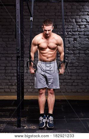 Portrait of young athlete man doing pull-ups with rings against brick wall in the cross fit gym. Sportsman in the grey sporty shorts and sportive shoes. Body, muscle and abs. Healthy lifestyle.