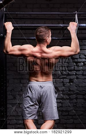 Rear view photo of muscular male doing exercises on horizontal bar against brick wall at the cross fit gym. Sportsman in the grey sportive shorts. Body and muscle. Power and energy. Healthy lifestyle.
