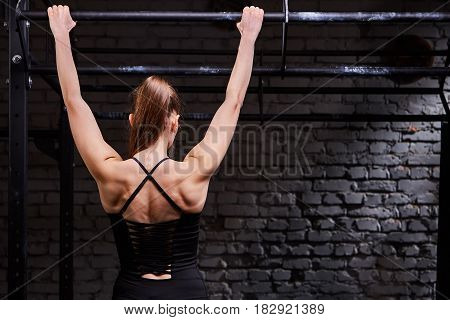 Rear view photo of young muscular woman doing exercises on horizontal bar against brick wall at the cross fit gym. Body and muscle. Power and energy. Healthy lifestyle.