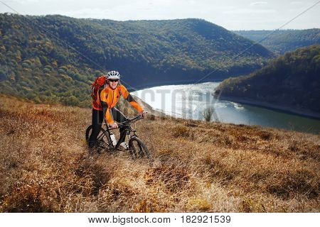 Cyclist in orange jacketr stands with his bike under river against beautiful landscape with mountain. Sportsman in the helmet, sunglasses and with red backpack. Summer season in the countryside. Concept of the extreme travel with bicycle.