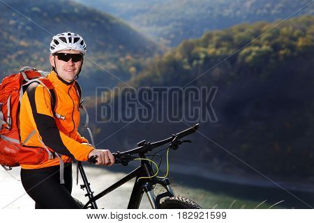 Close-up photo of cyclist in orange jacketr stands with his bike under river against beautiful landscape. Sportsman in the helmet, sunglasses and with red backpack. Summer season in the countryside. Concept of the extreme travel with bicycle.