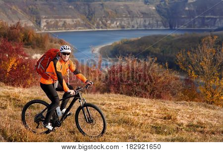 Cyclist in orange jacketr riding bike on the hill under river against beautiful landscape. Sportsman in the helmet, sunglasses and with red backpack. Summer season in the countryside. Concept of the extreme travel with bicycle.