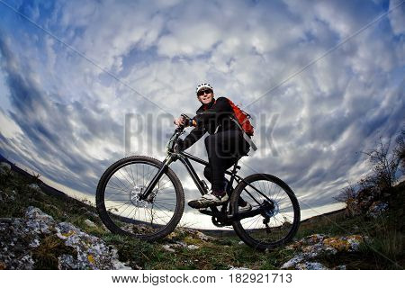 Cyclist in the black sportwear riding the bike on the rock at evening against beautiful blue sky with clouds. Sportsman in the helmet, sunglasses and with red backpack. Extreme travel in the countryside. Summer season. Healthy lifestyle. Fisheye.