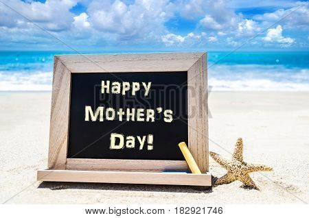 Happy Mother's day background with starfish on the sandy beach near the ocean