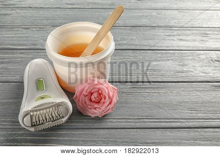 Modern epilator and plastic bucket with sugaring paste on wooden background