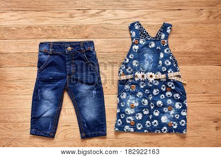 Children's jeans denim dress on wooden background. Blue dark jeans and denim dress in flowers with cute belt. Clothes for little girl. Casual and modern chidren's style.