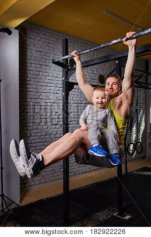 Young happy father doing pull ups on the bar with son on his legs at the cross fit gym against brick wall. Portrait of smiling father and his little son. Sportsman and child in the sportwear and shoes. Rearing child in the healthy lifestyle.