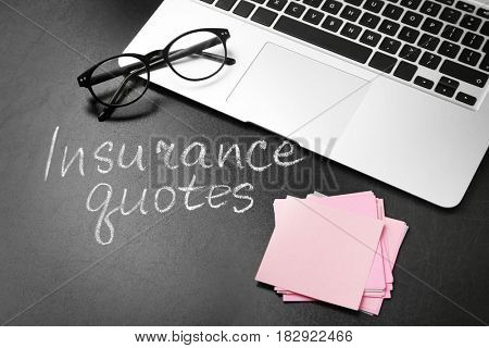 Text INSURANCE QUOTES, laptop and glasses on blackboard background