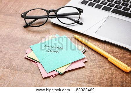 Paper note with text INSURANCE QUOTES and laptop on wooden background
