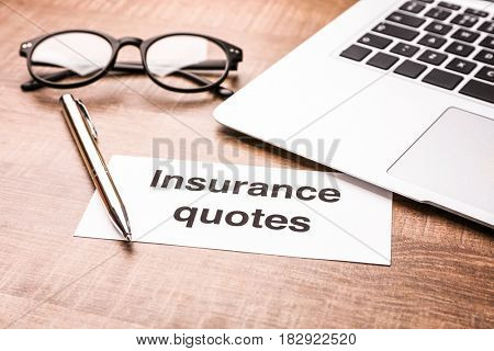 Card with text INSURANCE QUOTES, laptop and glasses on wooden background