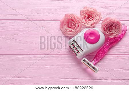 Epilator, razor and flowers on color wooden background