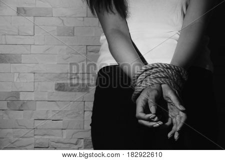 Woman with tied hands on brick wall background