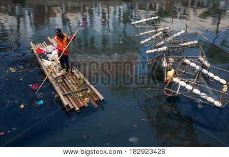 Jakarta, Indonesia - september 9, 2015: cleaning up a Jakarta canal on a raft in Kota Tua, Jakarta, Indonesia