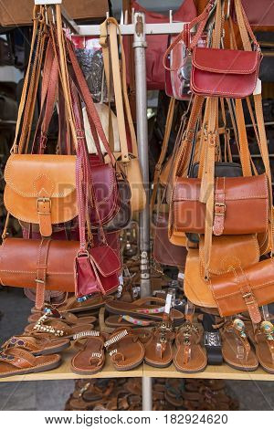 Leather bags and slippers on a market