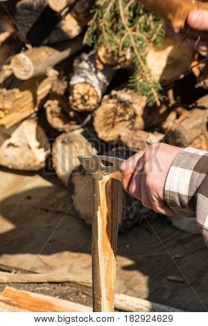 male splitting wood primitively with small log and hunting knife.