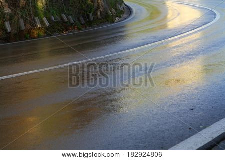 Asphalt road with a divided marge after rain.
