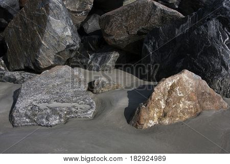 Rocks and boulders in the beach sands along the shore of the Atlantic Ocean in Jetty Park, Florida
