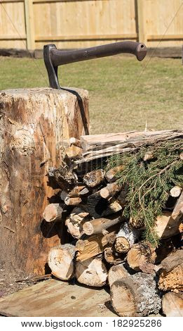 stack of camp fire wood with an axe in a tree stump.